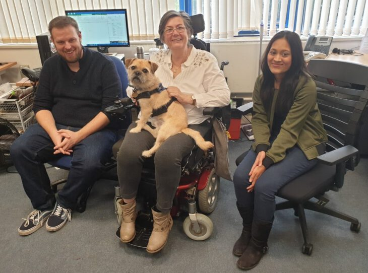 Judith Margolis in her wheelchair wearing a white shirt and grey jeans with her assistance dog on her lap and two colleagues either side